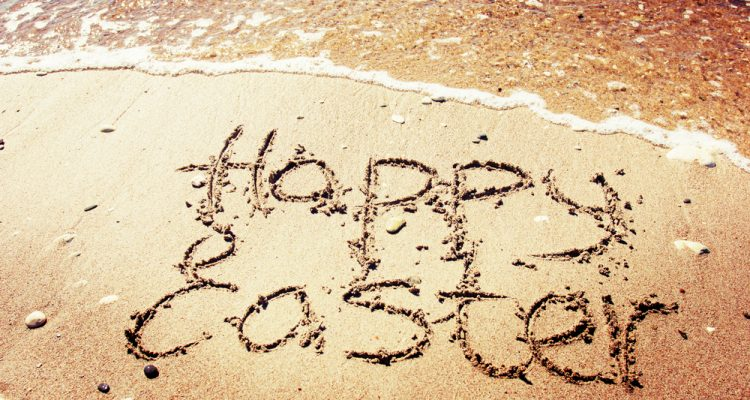 Happy Easter written on a sandy beach